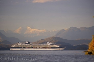 A cruiseship passes by the mountainous landscape that shines in the sunlight off Northern Vancouver Island in British Columbia, Canada.